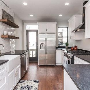 ボルチモアの広いインダストリアルスタイルのおしゃれなキッチン (アンダーカウンターシンク、シェーカースタイル扉のキャビネット、白いキャビネット、クオーツストーンカウンター、白いキッチンパネル、サブウェイタイルのキッチンパネル、シルバーの調理設備、無垢フローリング、茶色い床) の写真