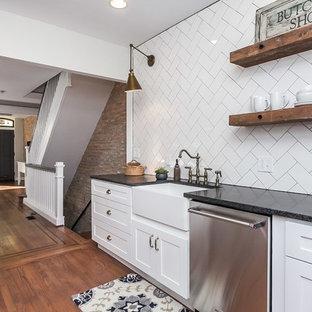 ボルチモアの大きいインダストリアルスタイルのおしゃれなキッチン (アンダーカウンターシンク、シェーカースタイル扉のキャビネット、白いキャビネット、クオーツストーンカウンター、白いキッチンパネル、サブウェイタイルのキッチンパネル、シルバーの調理設備の、無垢フローリング、茶色い床) の写真