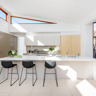 Inspiration for a contemporary galley open plan kitchen in Canberra - Queanbeyan with an undermount sink, flat-panel cabinets, beige cabinets, beige splashback, panelled appliances, with island, beige floor and white benchtop.