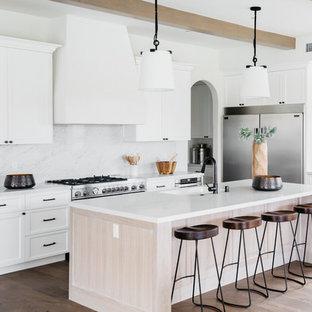 ロサンゼルスの地中海スタイルのおしゃれなキッチン (一体型シンク、シェーカースタイル扉のキャビネット、白いキャビネット、白いキッチンパネル、シルバーの調理設備、無垢フローリング、茶色い床、白いキッチンカウンター) の写真