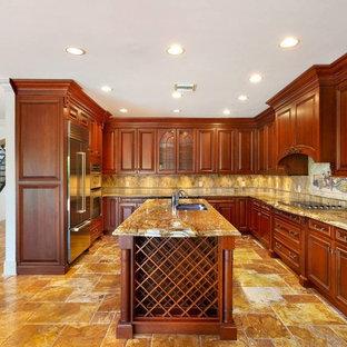 他の地域の中サイズの地中海スタイルのおしゃれなキッチン (アンダーカウンターシンク、レイズドパネル扉のキャビネット、中間色木目調キャビネット、オニキスカウンター、ベージュキッチンパネル、トラバーチンの床、シルバーの調理設備の、トラバーチンの床、黄色い床、黄色いキッチンカウンター) の写真