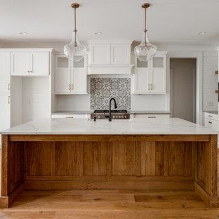 Modelo de cocina clásica renovada con fregadero sobremueble, armarios estilo shaker, puertas de armario blancas, encimera de cuarzo compacto, electrodomésticos de acero inoxidable, suelo de madera clara y encimeras blancas