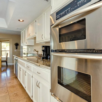 Example of a mid-sized tuscan galley travertine floor eat-in kitchen design in Phoenix with an undermount sink, recessed-panel cabinets, white cabinets, granite countertops, stainless steel appliances and an island