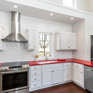 This is an example of a mid-sized modern l-shaped kitchen in Kansas City with an undermount sink, recessed-panel cabinets, white cabinets, quartz benchtops, white splashback, ceramic splashback, stainless steel appliances, bamboo floors, brown floor and red benchtop.