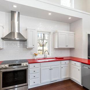 Свежая идея для дизайна: угловая кухня среднего размера в стиле модернизм с врезной раковиной, фасадами с утопленной филенкой, белыми фасадами, столешницей из кварцевого агломерата, белым фартуком, фартуком из керамической плитки, техникой из нержавеющей стали, полом из бамбука, коричневым полом и красной столешницей - отличное фото интерьера