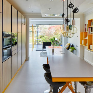 This is an example of a medium sized contemporary galley open plan kitchen in Hertfordshire with an island, flat-panel cabinets, beige cabinets, composite countertops, integrated appliances, grey floors and grey worktops.