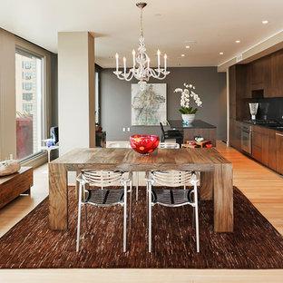 ポートランドのコンテンポラリースタイルのおしゃれなキッチン (フラットパネル扉のキャビネット、濃色木目調キャビネット、黒いキッチンパネル、パネルと同色の調理設備、ガラス板のキッチンパネル) の写真