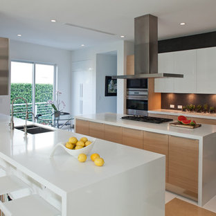 This is an example of a large contemporary galley eat-in kitchen in Miami with a double-bowl sink, flat-panel cabinets, light wood cabinets, stainless steel appliances, quartz benchtops, porcelain floors, with island and multi-coloured floor.