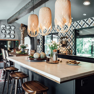 Inspiration for a mid-sized eclectic u-shaped eat-in kitchen in Salt Lake City with a drop-in sink, flat-panel cabinets, black cabinets, marble benchtops, multi-coloured splashback, stone tile splashback, panelled appliances, dark hardwood floors and multiple islands.