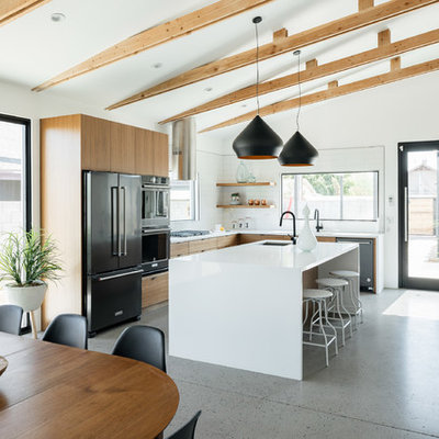 Kitchen - large contemporary l-shaped concrete floor and gray floor kitchen idea in Phoenix with flat-panel cabinets, white backsplash, stainless steel appliances, an island, white countertops, an undermount sink, medium tone wood cabinets, quartz countertops and ceramic backsplash