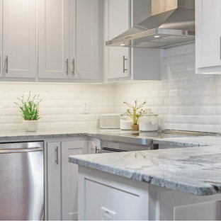This is an example of a small traditional u-shaped kitchen/diner in Dallas with a submerged sink, shaker cabinets, white cabinets, granite worktops, white splashback, metro tiled splashback, stainless steel appliances, medium hardwood flooring, a breakfast bar, brown floors and white worktops.