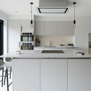 Mid-sized contemporary open concept kitchen designs - Example of a mid-sized trendy single-wall light wood floor and white floor open concept kitchen design in Sussex with a drop-in sink, flat-panel cabinets, gray cabinets, beige backsplash, ceramic backsplash and an island