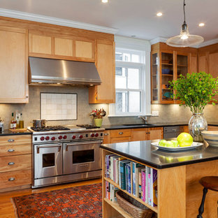 Inspiration for a mid-sized timeless u-shaped medium tone wood floor eat-in kitchen remodel in Boston with an undermount sink, medium tone wood cabinets, soapstone countertops, beige backsplash, subway tile backsplash, stainless steel appliances and an island