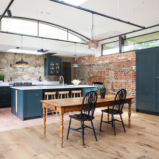 Inspiration for an expansive rural u-shaped kitchen/diner in Kent with granite worktops, black appliances, terracotta flooring, an island, multi-coloured floors, shaker cabinets, blue cabinets, an integrated sink and white worktops.