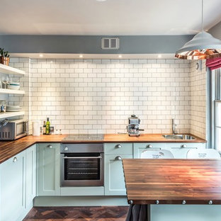 This is an example of a traditional eat-in kitchen in Edinburgh with a peninsula, shaker cabinets, blue cabinets, wood benchtops, white splashback, subway tile splashback and dark hardwood floors.