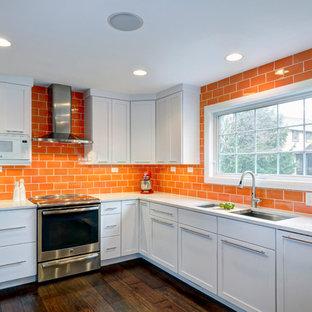 コロンバスのコンテンポラリースタイルのおしゃれなキッチン (アンダーカウンターシンク、フラットパネル扉のキャビネット、白いキャビネット、クオーツストーンカウンター、オレンジのキッチンパネル、セラミックタイルのキッチンパネル、シルバーの調理設備、濃色無垢フローリング) の写真