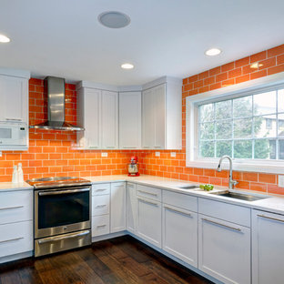 Photo of a contemporary l-shaped eat-in kitchen in Columbus with an undermount sink, flat-panel cabinets, white cabinets, quartz benchtops, orange splashback, ceramic splashback, stainless steel appliances, dark hardwood floors and a peninsula.