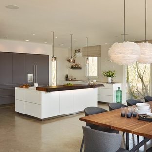 Large contemporary open concept kitchen photos - Example of a large trendy l-shaped concrete floor open concept kitchen design in Wiltshire with a double-bowl sink, flat-panel cabinets, white cabinets, quartz countertops, glass sheet backsplash, stainless steel appliances and an island