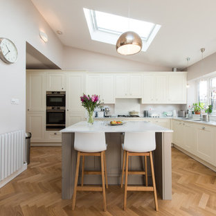 Design ideas for a medium sized traditional l-shaped open plan kitchen in London with a built-in sink, shaker cabinets, quartz worktops, stainless steel appliances, light hardwood flooring, an island and white worktops.