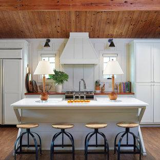 Mittelgroße, Zweizeilige Landhausstil Küche mit Landhausspüle, Schrankfronten im Shaker-Stil, weißen Schränken, Arbeitsplatte aus Holz, Elektrogeräten mit Frontblende, dunklem Holzboden, Kücheninsel und braunem Boden in Birmingham