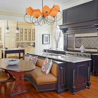 This is an example of an expansive traditional single-wall eat-in kitchen in Charleston with a single-bowl sink, raised-panel cabinets, granite benchtops, beige splashback, ceramic splashback, stainless steel appliances, medium hardwood floors, multiple islands, grey cabinets and beige floor.