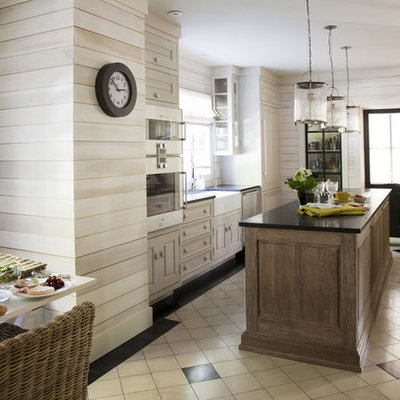 Example of a trendy eat-in kitchen design in Montreal with a farmhouse sink, raised-panel cabinets, light wood cabinets and paneled appliances