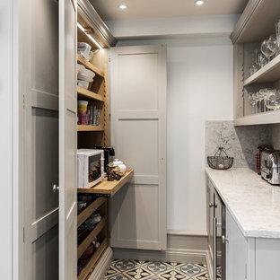 ケントの中サイズのカントリー風おしゃれなキッチン (一体型シンク、シェーカースタイル扉のキャビネット、グレーのキャビネット、珪岩カウンター、グレーのキッチンパネル、大理石のキッチンパネル、カラー調理設備、無垢フローリング、白いキッチンカウンター) の写真