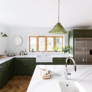 Idéer för att renovera ett stort lantligt vit vitt kök, med en rustik diskho, luckor med profilerade fronter, gröna skåp, bänkskiva i kvartsit, glaspanel som stänkskydd, svarta vitvaror, mellanmörkt trägolv, en köksö och brunt golv