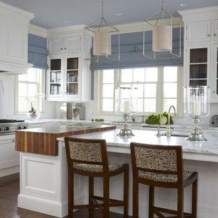 Große Klassische Wohnküche in U-Form mit Kassettenfronten, Arbeitsplatte aus Holz, weißen Schränken, Unterbauwaschbecken, Küchenrückwand in Weiß, Küchengeräten aus Edelstahl, Korkboden, Kücheninsel und braunem Boden in New York