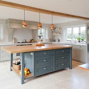 Lantlig inredning av ett stort kök, med släta luckor, blå skåp, bänkskiva i koppar, rostfria vitvaror, kalkstensgolv, en köksö och glaspanel som stänkskydd