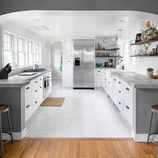 シアトルの中サイズのモダンスタイルのおしゃれなキッチン (エプロンフロントシンク、落し込みパネル扉のキャビネット、白いキャビネット、コンクリートカウンター、シルバーの調理設備の、セラミックタイルの床、アイランドなし、白い床、グレーのキッチンカウンター) の写真