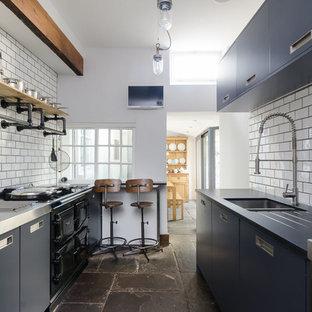 Zweizeilige Industrial Küche ohne Insel mit Doppelwaschbecken, flächenbündigen Schrankfronten, blauen Schränken, Edelstahl-Arbeitsplatte, Küchenrückwand in Weiß, Rückwand aus Metrofliesen und schwarzen Elektrogeräten in Sonstige