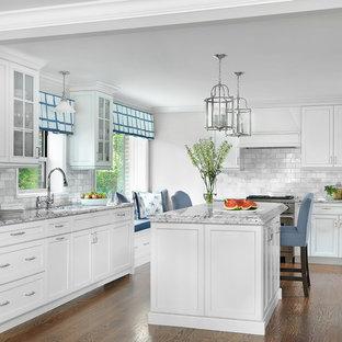Mittelgroße Klassische Küche mit weißen Schränken, Granit-Arbeitsplatte, Küchenrückwand in Grau, Küchengeräten aus Edelstahl, braunem Holzboden, Kücheninsel, Unterbauwaschbecken, Schrankfronten im Shaker-Stil, Rückwand aus Metrofliesen und grauer Arbeitsplatte in St. Louis