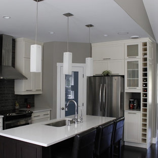 This is an example of a medium sized contemporary l-shaped kitchen pantry in Other with a submerged sink, shaker cabinets, white cabinets, quartz worktops, black splashback, glass tiled splashback, stainless steel appliances, dark hardwood flooring and an island.
