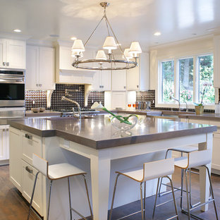Large contemporary eat-in kitchen appliance - Example of a large trendy u-shaped eat-in kitchen design in Las Vegas with stainless steel appliances, concrete countertops, a farmhouse sink, shaker cabinets, white cabinets, multicolored backsplash and an island