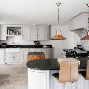Photo of a medium sized traditional u-shaped open plan kitchen in Kent with a belfast sink, shaker cabinets, grey cabinets, granite worktops, brown splashback, ceramic splashback, black appliances, limestone flooring, an island, beige floors and black worktops.