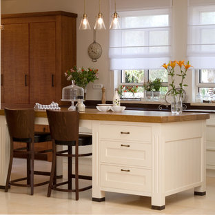 Mediterranean eat-in kitchen ideas - Example of a tuscan l-shaped eat-in kitchen design in Tel Aviv with wood countertops, white cabinets, a drop-in sink and shaker cabinets