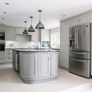 Design ideas for a mid-sized transitional u-shaped eat-in kitchen in Kent with a farmhouse sink, shaker cabinets, grey cabinets, granite benchtops, white splashback, subway tile splashback, panelled appliances, ceramic floors, with island, white floor and black benchtop.