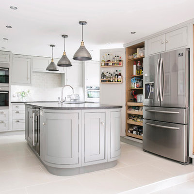 Example of a mid-sized classic u-shaped ceramic tile and white floor eat-in kitchen design in Kent with a farmhouse sink, gray cabinets, granite countertops, an island, white backsplash, shaker cabinets, subway tile backsplash, paneled appliances and black countertops