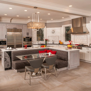 Large transitional l-shaped open plan kitchen in Detroit with an undermount sink, recessed-panel cabinets, white cabinets, quartz benchtops, white splashback, subway tile splashback, stainless steel appliances, ceramic floors and multiple islands.