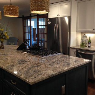 Photo of a mid-sized transitional l-shaped eat-in kitchen in Cleveland with a farmhouse sink, recessed-panel cabinets, granite benchtops, beige splashback, porcelain splashback, stainless steel appliances, dark hardwood floors, with island and white cabinets.