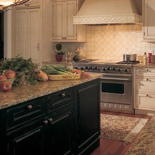 ミネアポリスの大きいエクレクティックスタイルのおしゃれなキッチン (ドロップインシンク、レイズドパネル扉のキャビネット、ヴィンテージ仕上げキャビネット、御影石カウンター、白いキッチンパネル、セラミックタイルのキッチンパネル、パネルと同色の調理設備、無垢フローリング) の写真
