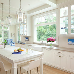 Idéer för att renovera ett mellanstort vintage kök med öppen planlösning, med en rustik diskho, skåp i shakerstil, vita skåp, ljust trägolv, en köksö, marmorbänkskiva, vitt stänkskydd, stänkskydd i sten och rostfria vitvaror