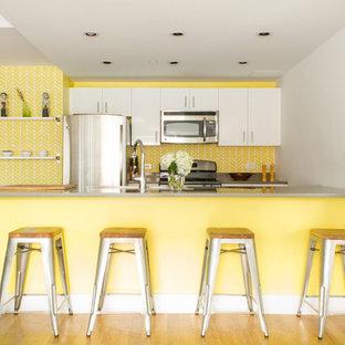 Imagen de cocina comedor lineal, moderna, de tamaño medio, con fregadero encastrado, armarios con paneles lisos, puertas de armario blancas, encimera de acrílico, salpicadero amarillo, electrodomésticos de acero inoxidable, suelo de madera clara y una isla