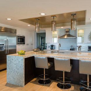 Пример оригинального дизайна интерьера: большая угловая кухня-гостиная в современном стиле с врезной раковиной, фасадами в стиле шейкер, столешницей терраццо, серым фартуком, фартуком из керамической плитки, техникой из нержавеющей стали, полом из керамогранита и островом