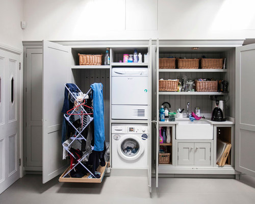 Trendy laundry closet photo in London with a stacked washer/dryer