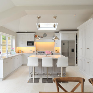 This is an example of a medium sized traditional u-shaped kitchen/diner in London with recessed-panel cabinets, granite worktops, stainless steel appliances, limestone flooring and an island.