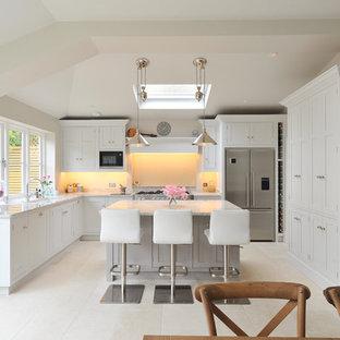 Idéer för ett mellanstort klassiskt kök, med luckor med infälld panel, granitbänkskiva, rostfria vitvaror, kalkstensgolv och en köksö