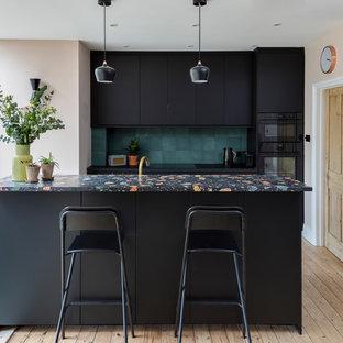 Diseño de cocina escandinava con armarios con paneles lisos, puertas de armario negras, salpicadero gris, electrodomésticos negros, suelo de madera clara, una isla, suelo beige, encimeras multicolor y encimera de terrazo