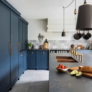 Große Industrial Wohnküche in U-Form mit Doppelwaschbecken, Schrankfronten im Shaker-Stil, blauen Schränken, Mineralwerkstoff-Arbeitsplatte, bunter Rückwand, Rückwand aus Keramikfliesen, schwarzen Elektrogeräten, Porzellan-Bodenfliesen, Kücheninsel, grauem Boden und schwarzer Arbeitsplatte in Essex